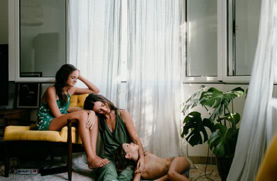 portrait d'une maman avec ses deux filles. Maman est assise par terre, adossee au mur, la tete sur sa plus grande qui est asssie dans une fauteuil jaune. la plus petite fille est allongee sur la maman